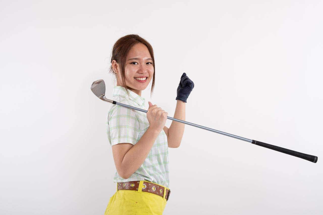 ゴルフクラブを持って笑顔の女性